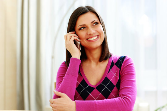 Middle-aged cheerful woman talking on the phone and looking away