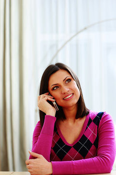 Middle-aged smiling woman talking on the phone and looking away