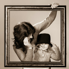 Mother and daughter posing with frame