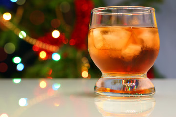 whiskey with ice against festive lights background