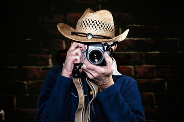 Man wearing cowboy hat photographing with vintage film camera