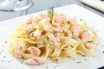 pasta con salmone piatto bianco sfondo grigio