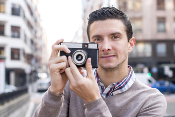 Portrait of photographer with retro camara in the street.