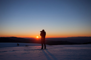 silhouette of photographer in sunset in winter landscape