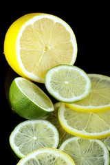 slices of lime and lemon on black background