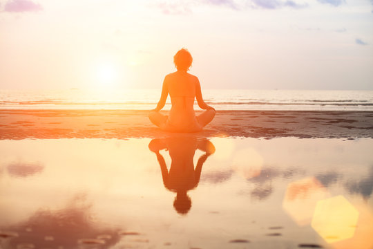 Yoga woman sitting in lotus pose on the beach during sunset.