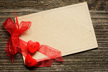 Two hearts tied with red ribbon