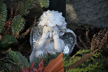 Trauriger Engel auf Friedhof hält sich die Augen zu