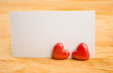 red hearts and note on wooden background