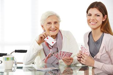 Wall Mural - Junge Frau spielt Karten mit Seniorin