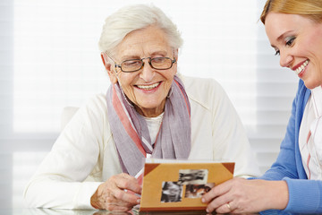 Seniorin schaut Fotos an mit Tochter