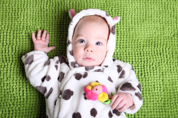 baby on a background of green grass in a cow kostbme