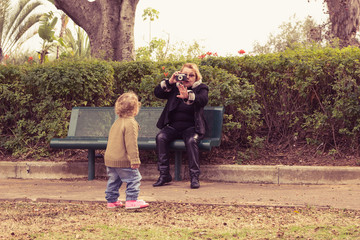 Grandmother photographing baby girl at a park