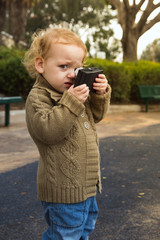 Adorable little baby holding vintage camera. Photo in old color