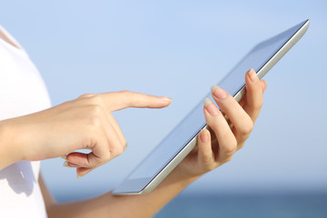 Woman hands holding and browsing a digital tablet on the beach
