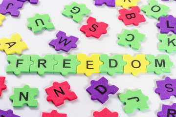 word FREEDOM formed with colorful foam puzzle  on white backgrou