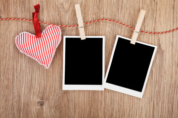Blank instant photos and red heart hanging on the clothesline