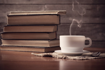 old books on wooden background with cup of coffee