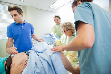Medical Team Examining Pregnant Woman During Delivery In Operati