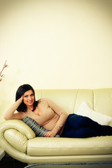 Portrait of a middle-aged happy woman lying on the sofa