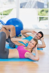 Portrait of a young couple exercising at gym