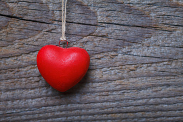 red heart hanging before wooden board