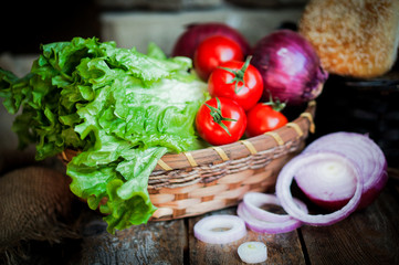 Fresh vegetables in the basket on wooden background