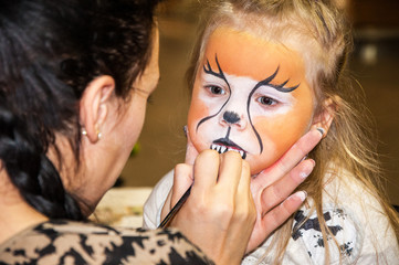 mother is preparing make-up for her daughter for a party