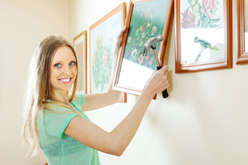 Positive beautiful woman hanging the art pictures