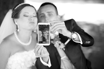 Young just married couple taking pictures of themselves