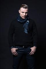 Man winter fashion. Wearing black sweater and scarf. Blonde hair