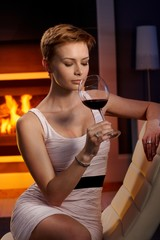 Sexy woman enjoying glass of wine