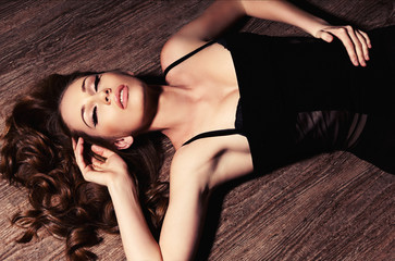 sexy girl in black dress lying on the wood floor