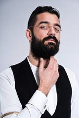 Retro hipster 1900 fashion man with black hair and beard. Wearin