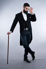 Retro hipster 1900 fashion man with black hair and beard. Standi