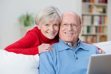 älteres ehepaar sitzt mit laptop auf dem sofa
