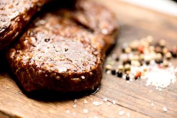 grilled steaks on an old board macro