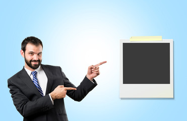 Businessman pointing to a photo over blue background