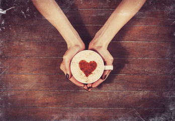 woman holding hot cup of coffee, with heart shape