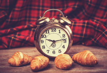 Retro alarm clock with croissant on a table.
