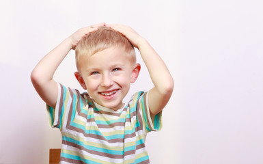 Portrait of surprised emotional blond boy child kid at the table