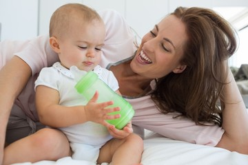Mother with baby holding milk bottle on bed