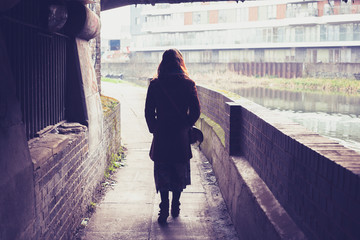 Young woman walking by canal under a bridge