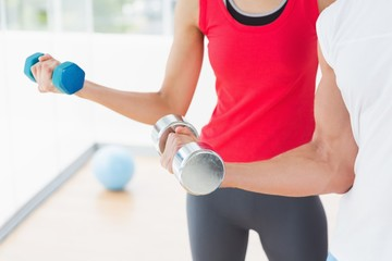 Mid section of a sporty couple with dumbbells