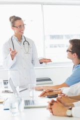 Happy doctor discussing with colleagues