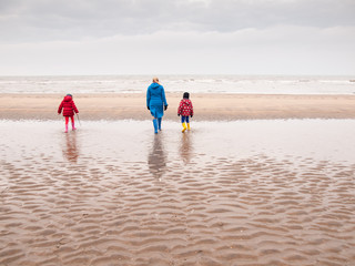 woman and two small children on winter beach