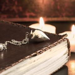 Pendel auf einem Buch mit Ledereinband
