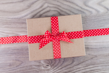 Small brown gift wrapped in red ribbon