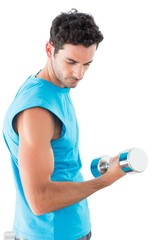 Serious young man exercising with dumbbell