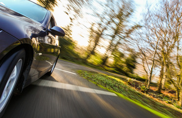 Fototapete - Front side view of speeding car.
